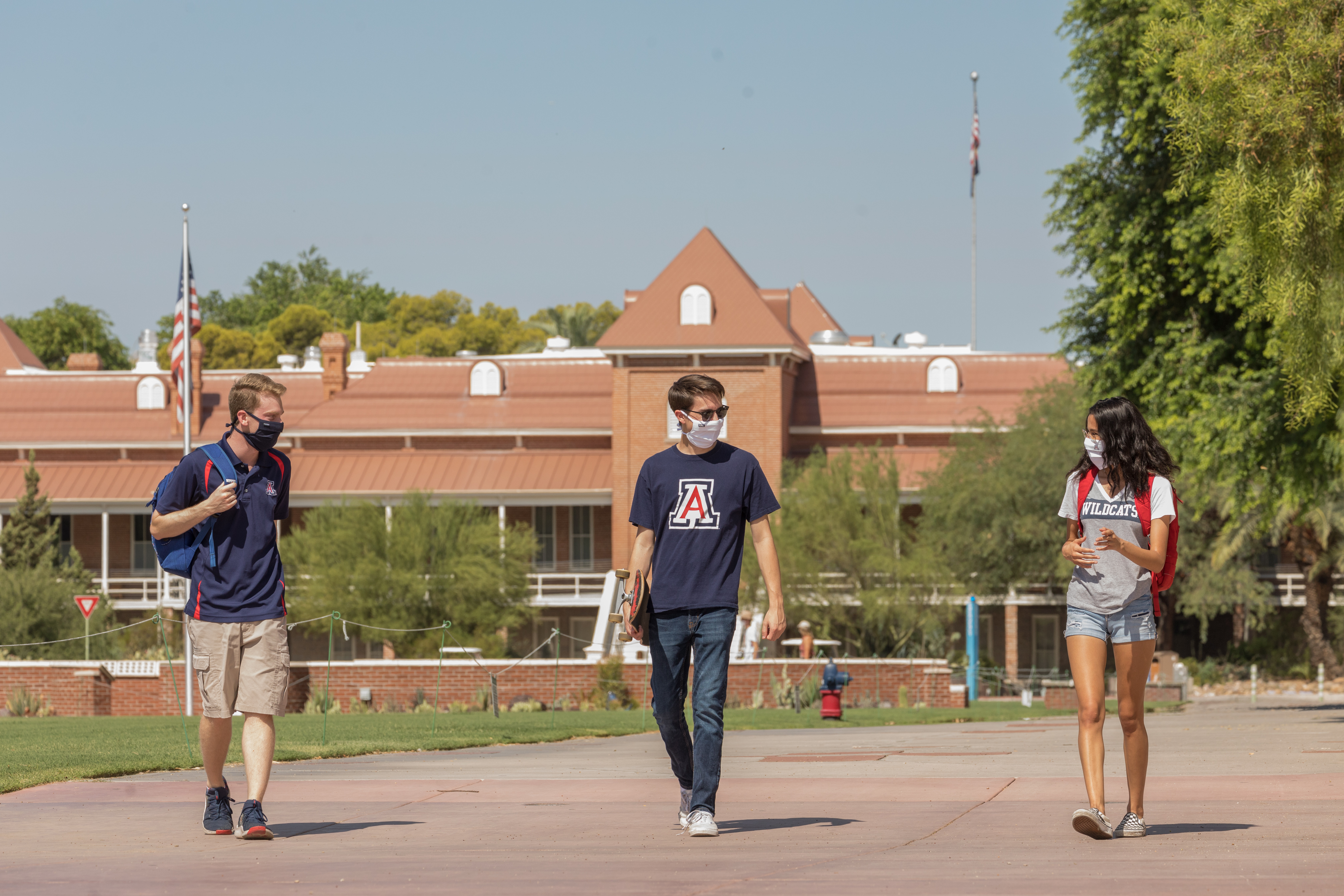 three students wearing face coverings walking in front of Old Main