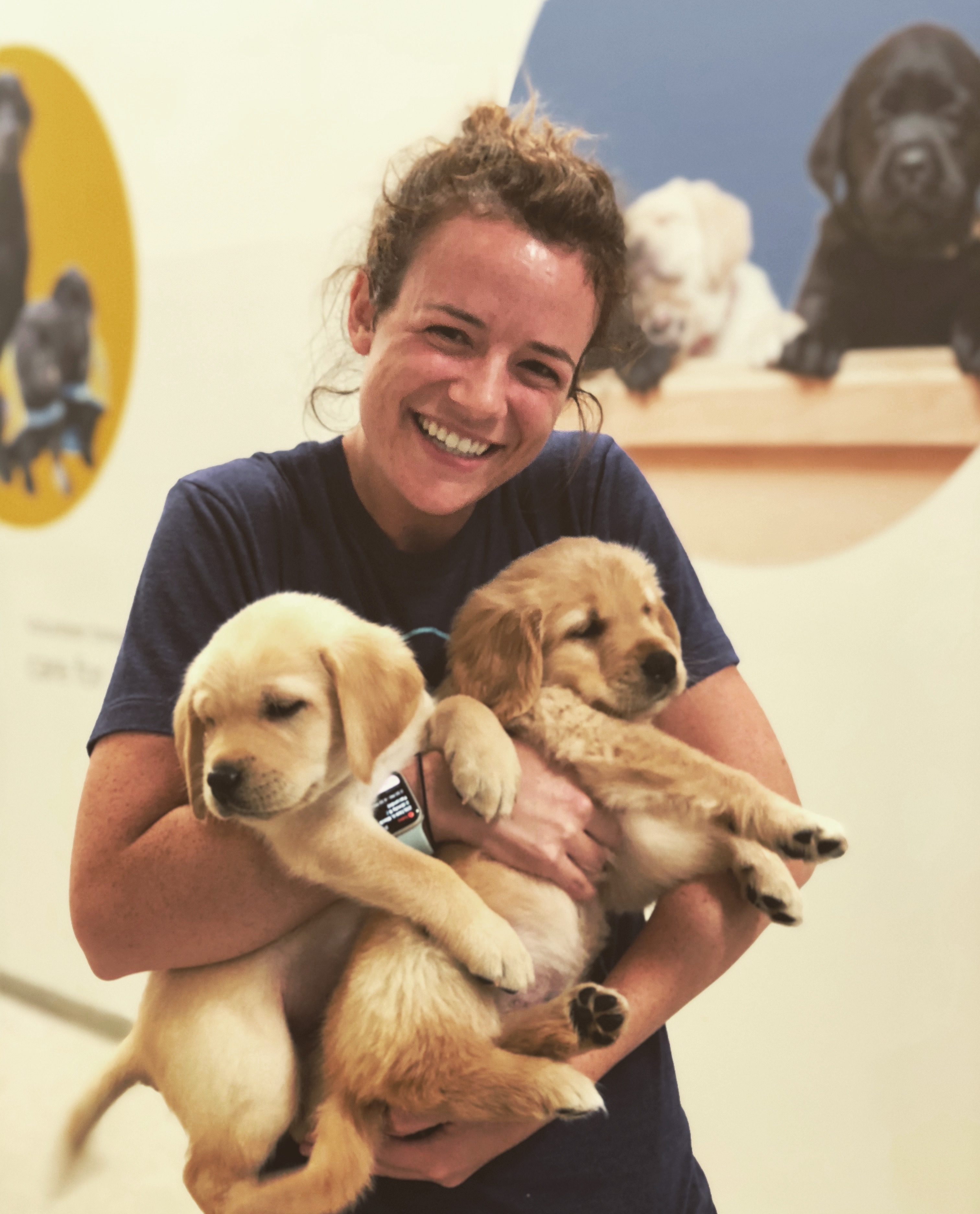 young woman holding two puppies