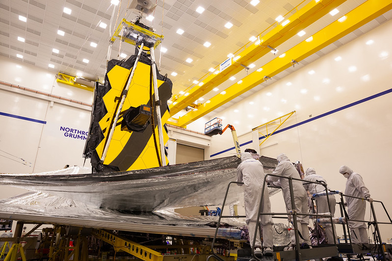 Technicians and engineers work on the James Webb Space Telescope, preparing its sunshield to be folded.