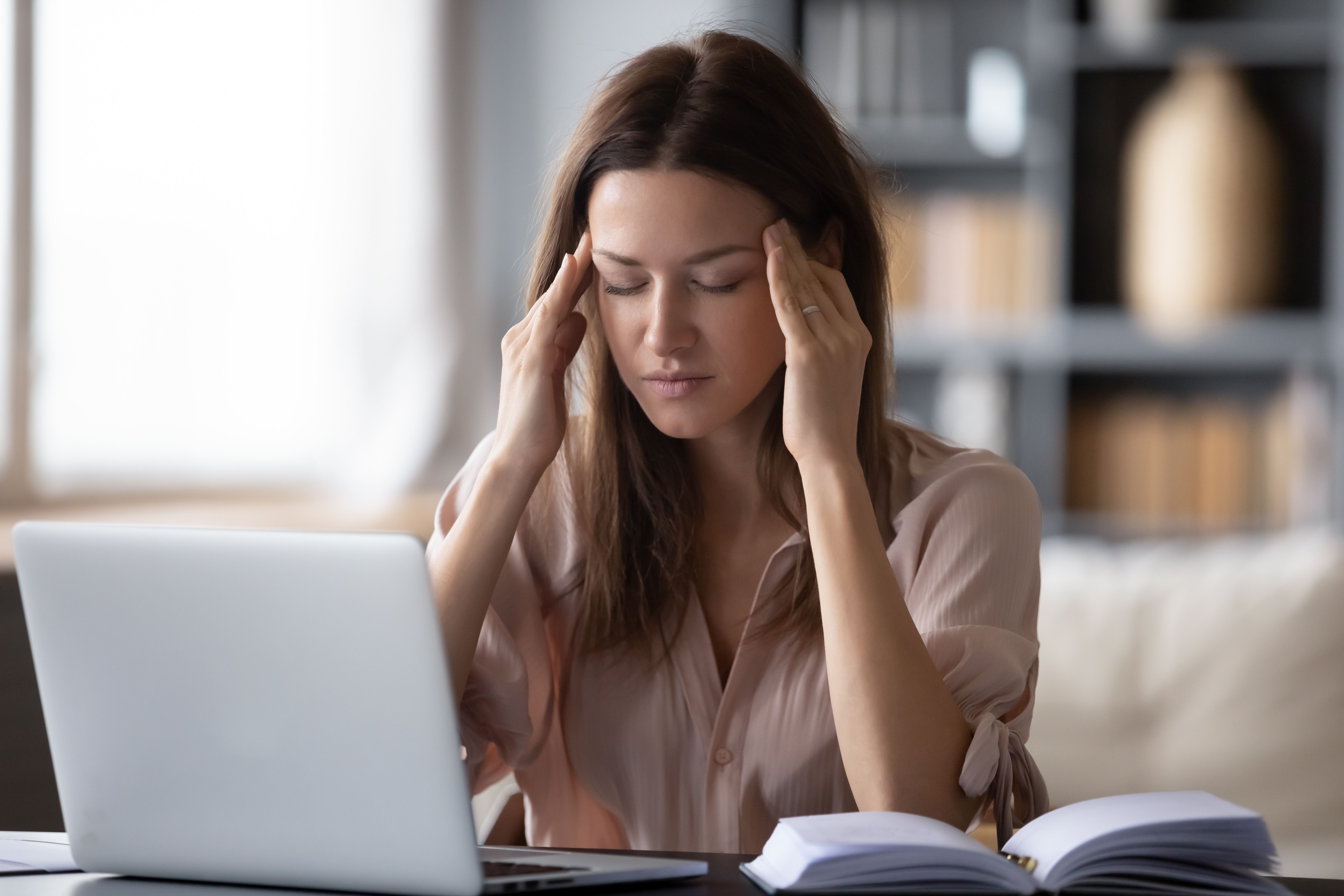 woman with a laptop rubbing her temples