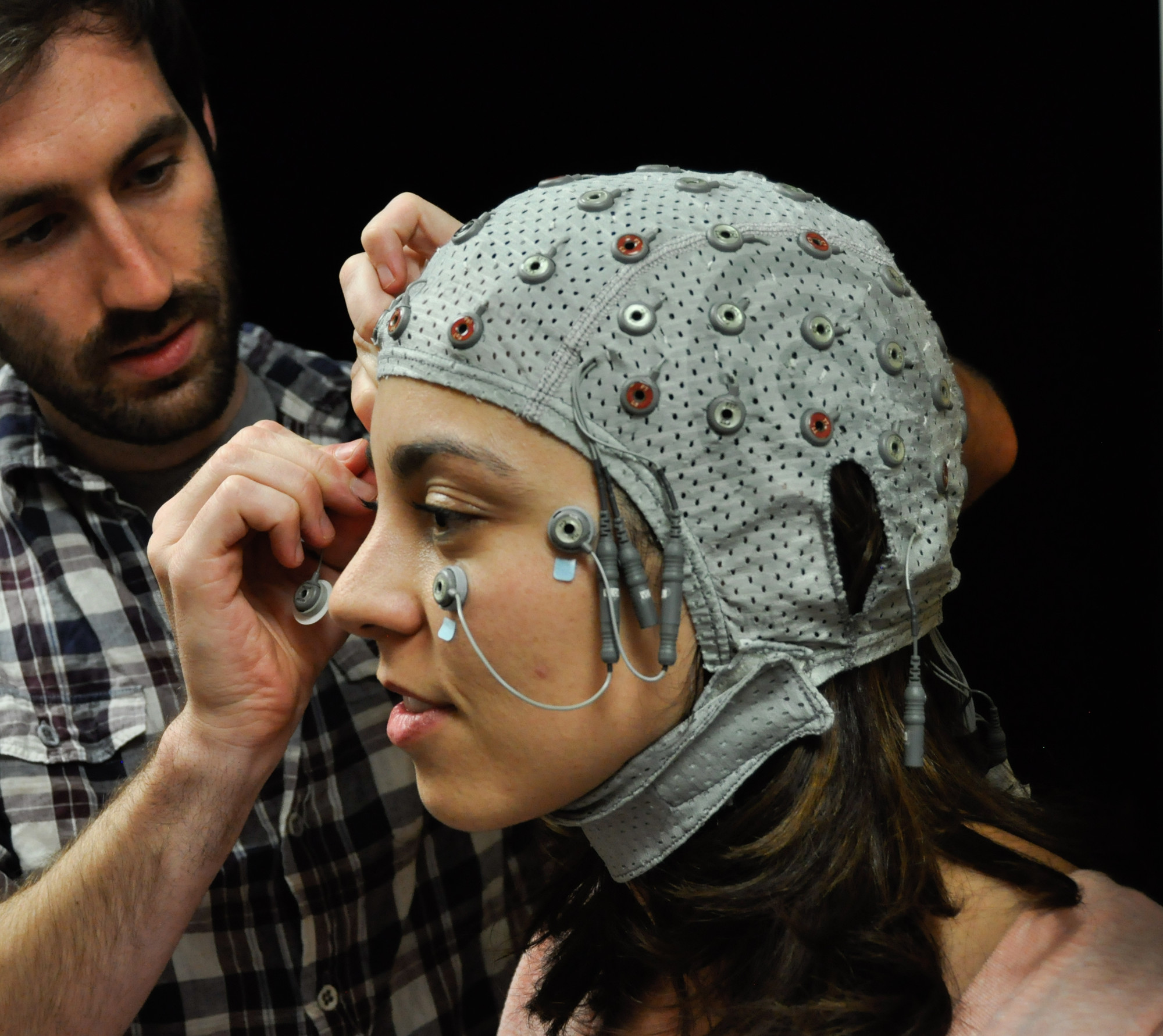 A look inside the mind: Davi Vitela dons a cap used to take EEG scans of her brain activity while she views a series of images. Jay Sanguinetti's study indicates that our minds perceive objects in everyday life of which we are never consciously aware.