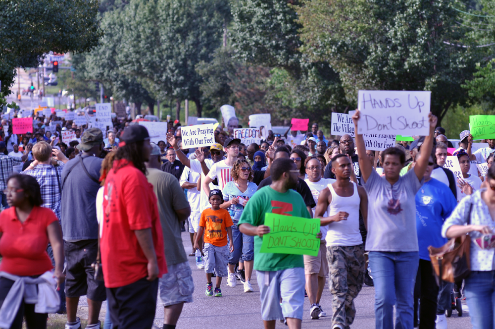 Protesters march in the aftermath of the Aug. 9 shooting death of Michael Brown in Ferguson, Mo.