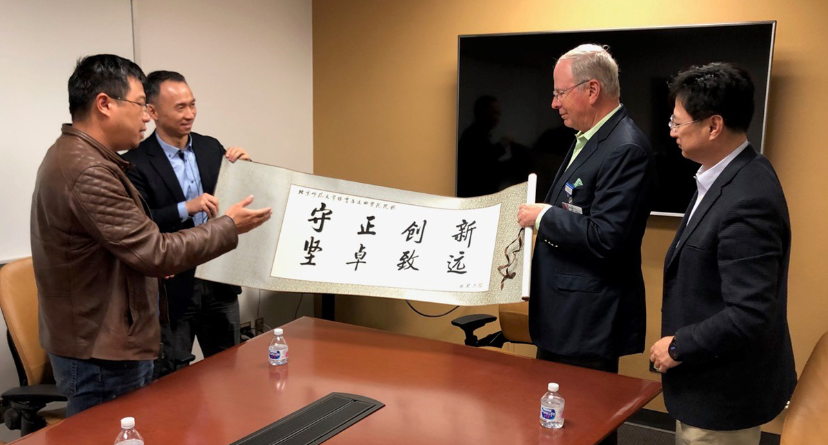 "Professors GuoFeng Qu  and ShaoJun Lyu , of Beijing Normal University, present a banner with their college motto – ""Steadfastness and Innovation, Resilience and Future"" – to Dr. Irving Kron , interim dean of the UA College of Medicine – Tucson, and UA lib"