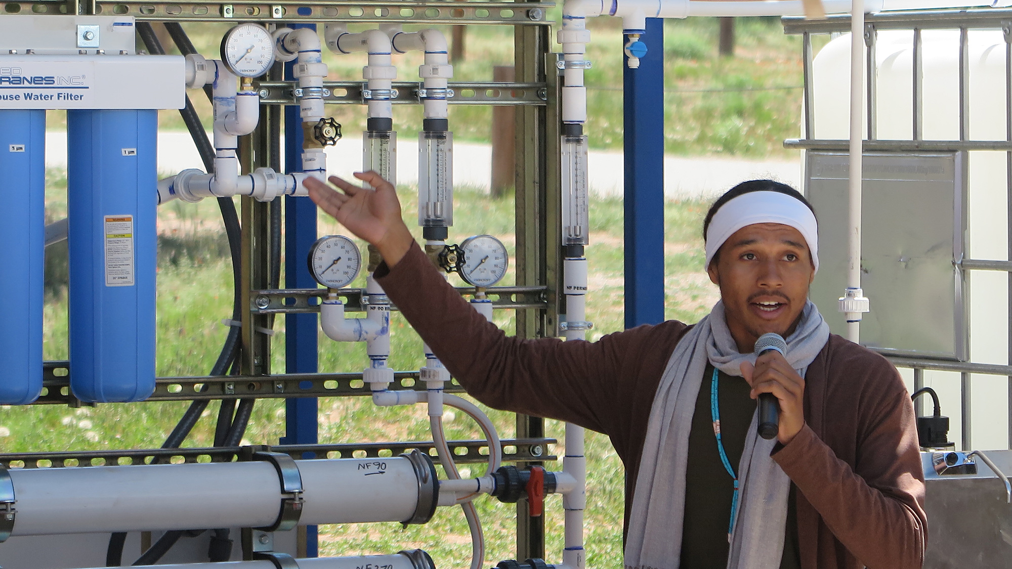 Diné College student and Indige-FEWSS participant Larry Moore demonstrates use of the solar-powered water filtration system to community members on Navajo Nation.