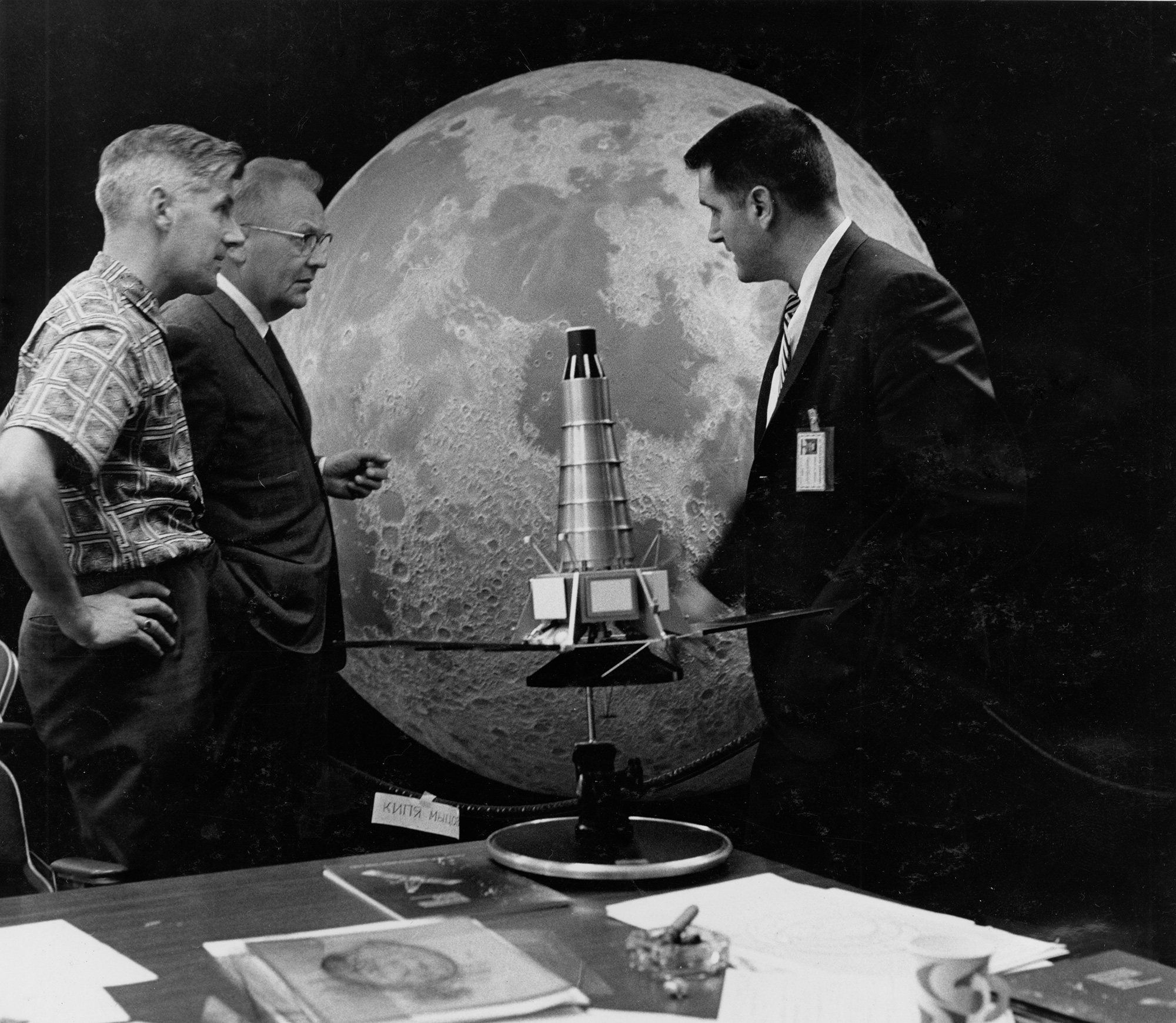"""Ewen Whitaker, Gerard Kuiper and Ray Heacock are pictured in front of a Ranger model and lunar hemisphere, which is now located at the Flandrau Science Center and Planetarium at the University of Arizona. A sign in front of half-globe reads """"keep yer mitt"""