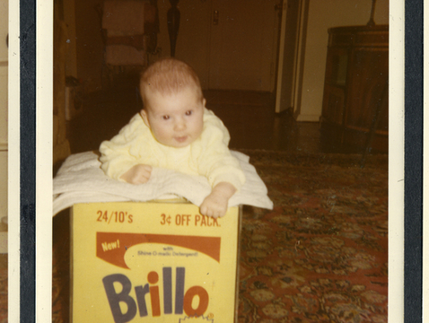 """Baby Lisanne Skyler and the Brillo Box from """"Brillo Box (3¢ Off)."""" From the Andy Warhol Foundation for the Visual Arts Inc. (Brillo trademark used with permission of Armaly Brands Inc.; photo courtesy of HBO)"""