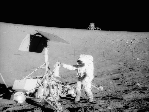 Charles Conrad examines Surveyor's TV camera prior to detaching it on Nov. 20, 1969. The Apollo 12 lunar module is in the background. (Image: NASA)