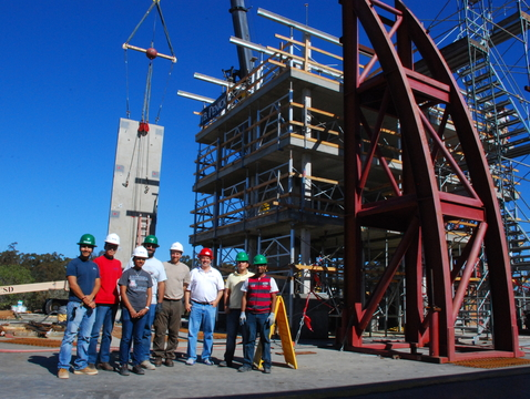 Robert Fleischman and members of his research team stand dwarfed by a test structure built on the shake table at UC San Diego's Englekirk Structural Engineering Center.