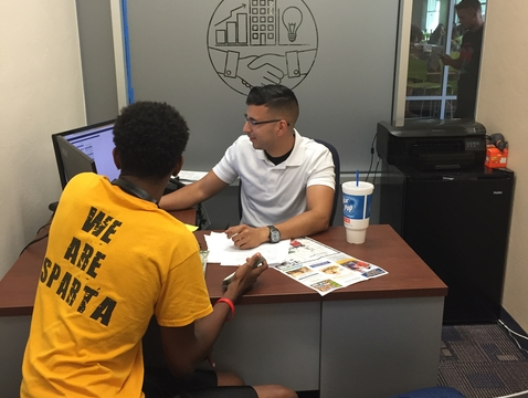 Ramses Sepulveda, project coordinator, helps a first-year student navigate a UAccess account. Sepulveda was stationed at the SOS desk on the first day of the fall semester to answer questions. (Photo courtesy of Jenny Nirh)
