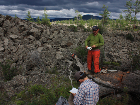 Kevin Anchukaitis (plaid shirt) and Oyunsanaa Byambasuren take cross-sections of dead trees on Mongolia's Uurgat lava field. The researchers used tree rings to create a record of Mongolia's droughts stretching 2,060 years into the past. (Photo: Neil Pederson © 2013)