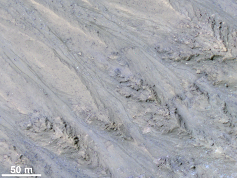 """This 2011 view near the top of the southern rim of Tivat Crater comes from the HiRISE camera on NASA's Mars Reconnaissance Orbiter. It shows the inner slope of a crater on southern Mars with several of the seasonal dark streaks called """"recurrent slope lineae,"""" or RSL. A November report interprets those as granular flows, rather than darkening due to flowing water. (Image: NASA/JPL-Caltech/UA/USGS)"""