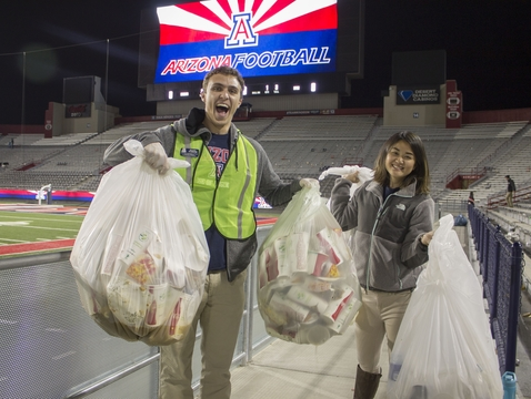 Students for Sustainability members Michael Rabbani (left) and Stephanie Choi collect bags of compostable items after Arizona's win against Utah on Nov. 14. (Photo: Rachel Spitz)