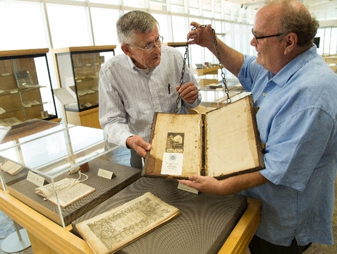 "Carl Berkhout (left) and Special Collections librarian Roger Myers examine the cover of a copy of the 1632 edition of ""A continuation of the histories of foreign martyrs."""