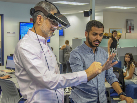 International student Hazza Alkaabi (right) helps UA honorary degree recipient Mohammed Sharaf experience augmented reality.