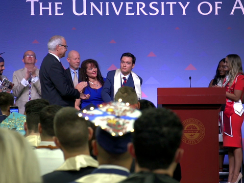 After spending most of his life in a wheelchair, Jeffrey Bristol (center) was able to stand to receive his UA diploma. (Photo: Bob Demers/UANews)