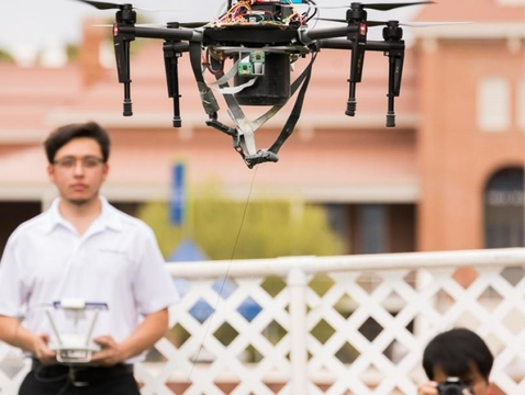 A student demonstrates his team's drone-mounted pollen dispenser at Engineering Design Day. (Photo: Chris Richards/UA Alumni Association)