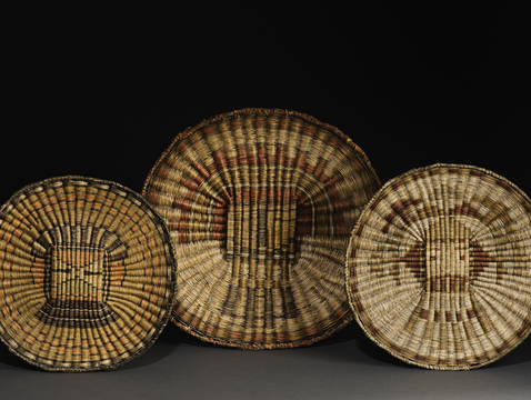 Wicker plaques from Third Mesa, made from rabbitbrush, dune broom and yucca, from left: Hiilili katsina, ca. 1935; Si'ohemiskatsina (Zuni Hemis katsina), ca. 1910; Sa'lakwmana (Shalako maiden katsina), ca. 1905. (Photo courtesy of Arizona State Museum)