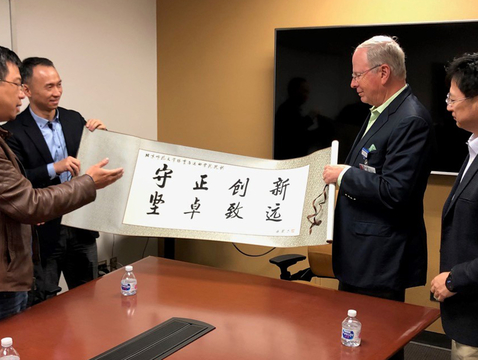 "Professors GuoFeng Qu (second from left) and ShaoJun Lyu (right), of Beijing Normal University, present a banner with their college motto – ""Steadfastness and Innovation, Resilience and Future"" – to Dr. Irving Kron (second from right), interim dean of the UA College of Medicine – Tucson, and UA librarian Yan Han (left)."