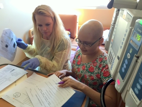 Teacher Ashley Brock reviews homework with Danitza Barra, a patient at Diamond Children's.