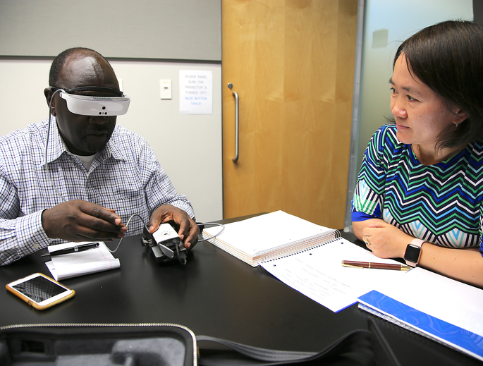 Kennedy Nyairo, Tech Launch Arizona licensing manager for the College of Optical Sciences, gets a demo of the eSight system from inventor Hong Hua. (Photo: Paul Tumarkin/Tech Launch Arizona)