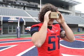 UA linebacker Jason Sweet uses an iPhone and Google Cardboard to play BrainGainz. (Photo: Emily Litvack/UA Office for Research & Discovery)