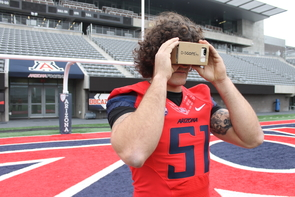 UA linebacker Jason Sweet uses an iPhone and Google Cardboard to play BrainGainz. (Photo: Emily Litvack/UA Office for Research & Discovery)