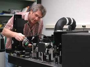 Robert Downs adjusts a piece of the mineral corundum in a Raman spectrometer. Rubies are red-colored corundum; sapphires are blue-colored corundum. Photo courtesy of the Downs laboratory, The University of Arizona.