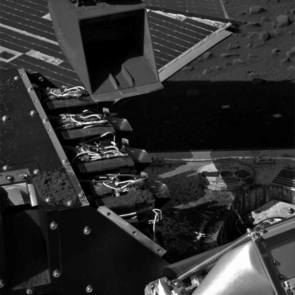 This image taken by the Surface Stereo Imager on NASA's Phoenix Mars Lander shows the lander's Robotic Arm scoop positioned over the Wet Chemistry Lab Cell 1 delivery funnel on Sol 41, the 42nd Martian day after landing, or July 6, 2008, after a soil sample was delivered to the instrument.