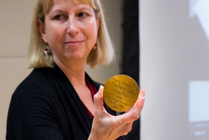 Karen Williams, dean of University Libraries, holds a bronze medallion. The medallions, inscribed with the names of the 1,177 sailors and Marines who lost their lives onboard the USS Arizona, will be part of the memorial. (Photo: Ernesto Trejo/UANews)