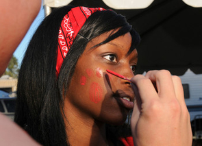 UA students in the ZonaZoo section of the stadium put on their game face to show support for the football team at the 2010 homecoming game. Shira Williams, a UA student studying public health, has the image of a Wildcat paw print painted on her face during last year's Homecoming event. (Photo credit: Norma Jean Gargasz/UANews)