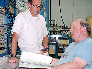 Gregory Hodgins (left), assistant research scientist, and  A. J. Tim Jull, director of the National Science Foundation-Arizona AMS Laboratory, discuss radiocarbon age results. The laboratory is jointly operated by the physics and geosciences departments at The University of Arizona in Tucson. (Photo: Lori Stiles)