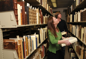 Chrystal Carpenter, the manuscript and congressional archivist for Special Collections, and student employee Jason Seamon look for works from the Oberman Research Library. (Photo credit: Norma Jean Gargasz/UANews)