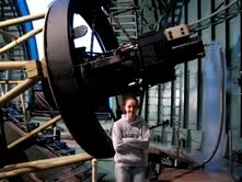 Black as the night sky into which the astronomers peer, the 90Prime camera sits mounted atop the UA's 90-inch telescope on Kitt Peak. UA astronomer Edward Olszewski's daughter, Cynthia Olszewski, stands beside the instrument. (Photo by Jill Bechtold)