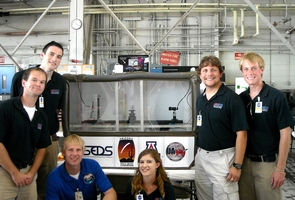 Once united for the UA's ASCEND project that sent a high-altitude weather balloon into the Earth's atmosphere, the members of team ANGEL again came together for NASA's reduced gravity program. The team stands with their payload for the zero gravity flight and with NASA mentor Chris Johnson. Pictured from left to right: Kevin Newman, Kyle Stephens, Chris Johnson, Sara Meschberger, Nathan Mogk and Sean Gellenbeck. (Credit: Shelley Littin/UANews)