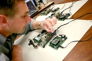 Kevin Carr, an undergraduate in electrical and computer engineering, adjusts one of the transmitter modules that is used to wirelessly link five units being tested in a self-healing computer system. The unit to the left of the transmitter is a Field Programmable Gate Array. Other transmitters and FPGAs can be seen in the background. (Photo by Matt Brailey)