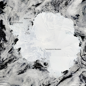 "The Moderate Resolution Imaging Spectroradiometer on NASA's Aqua satellite captured this composite image of Antarctica's ice-covered landscape on Jan. 27, 2009. The surface appears rough where the Transantarctic Mountains curve in a shallow ""s"" from the shore of the Ross Sea to the Ronne Ice Shelf. The Polar Plateau in the center of the continent is smooth, shaded only by the faint shadow cast by clouds. The Weddell Sea is textured with chunks of sea ice. (Photo Credit: NASA image courtesy the MODIS Rapid Response Team at NASA GSFC)"