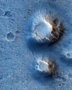 If the two crater- or volcano-like features dominating this HiRISE image are indeed ancient volcanoes, the blue color would indicate basalt, a telltale sign of having a volcanic origin. This image is about half a mile across. (Photo: NASA/JPL/UA)
