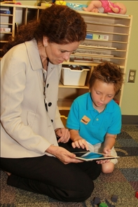 Dr. Sydney Rice with a patient using an iPad during a routine visit.