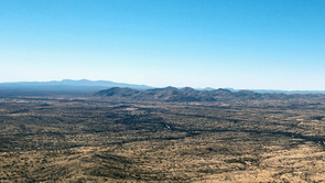 """When viewed from the top of a mountain in the Buenos Aires National Wildlife Refuge, the border wall becomes a thin black line that is almost invisible against the seamless landscape of the Sonoran Desert. """"Ecologically, the border does not exist,"""" Benjamin Wilder says. (Photo: Emily Walla/UANews)"""