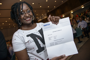 Charity Adusei, who moved to Arizona at age 17 with her family from Ghana in West Africa, proudly displays the letter showing she matched with the pediatrics residency program at Phoenix Children's Hospital. The first in her family to graduate from college, she will receive a dual MD-MPH degree from the UA in May. (Photo: Kris Hanning/UAHS BioCommunications).