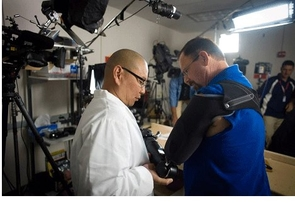 Dr. Albert Chi (left) assists patient Johnny Matheny with the robotic Modular Prosthetic Limb. Matheny lost most of his left arm to cancer five years ago