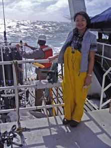 """Li Deng, co-first author on the Nature paper, stands on the deck of the research vessel """"Western Flyer"""" in front of the sampling device used to measure salinity, temperature and depth of the ocean during sample collection. (Photo: Sullivan lab)"""