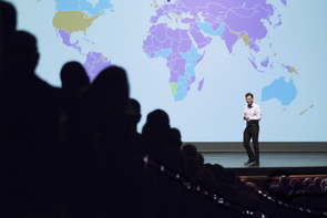Luis von Ahn stands in front of a map showing Duolingo's reach worldwide. The purple regions are where English is the dominant language being learned on Duolingo. The gold is for Spanish, the blue for French. (Photo: Bob Demers/UANews)