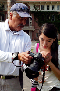 Fred Araiza shares his photo with Lexie Alvarez, a Tucson High School student and participant in the 10-day diversity workshop. (Photo credit: Iman Hamdan, UA School of Journalism)