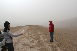 During a windstorm on China's Loess Plateau, geoscientist Fulong Cai uses a plastic bag as a wind sock to show that the wind blows parallel to the linear ridge he and Wang Zhao are standing on. Roads in this area run along the ridges. (Photo Credit: Paul Kapp/ UA Department of Geosciences)