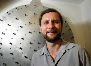 (Click to enlarge) A prototype of the adaptive mirror can be seen behind study leader Michael Hart. Controlled by a computer, the actuators warp the mirror ever so slightly to cancel out atmospheric blurring. (Photo credit: Norma Jean Gargasz / UANews)