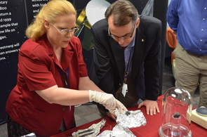 Dolores Hill, pictured here with OSIRIS-REx Principal Investigator Dante Lauretta, carefully handles a meteorite during an outreach event.