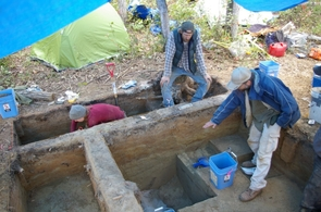 Josh Reuther (seated) and University of Alaska professor Ben Potter (right) examine the pit house they excavated at the Upward Sun River site in Alaska. (Photo courtesy Vance Holliday)