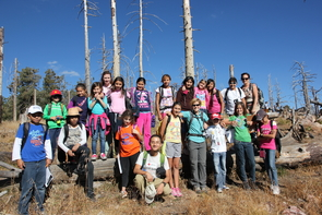 Pacifica Sommers (fourth from right, in blue) created a curriculum of activities and games to allow the students to explore the environment on Mt. Lemmon. For many trip participants, this was the first time they had journeyed outside of the city streets. (Photo by Alan Strauss
