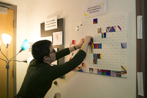 """Organizer Hannah Tanquary pins up another segment of the """"Equation Art Intervention."""" The attendees were invited to color a segment of the equation to add to the board. A picture of the completed result can be found on the event's website. (Photo: Mallory Shibe)"""